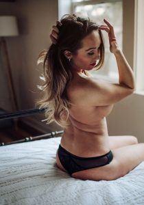 Woman sitting up in bed with her hands in her hair, Kitsap WA Boudoir Photography
