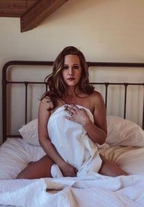 Kitsap WA Boudoir Photography, woman on her knees in the middle of the bed covered up with a sheet