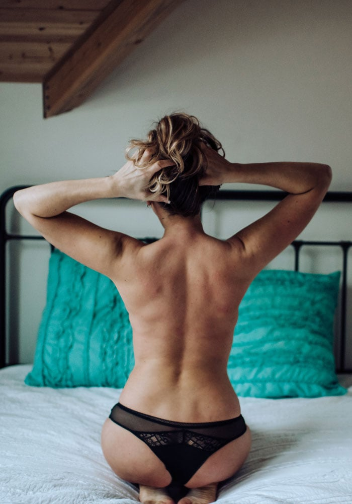 Kitsap WA Boudoir Photography, image of a woman's bare back in bed with her hair up