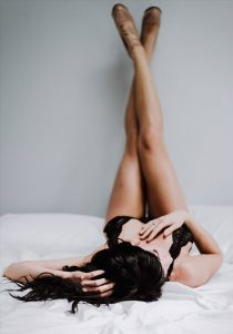 Kitsap WA Boudoir Photography, woman in black lingerie with her legs up on the wall
