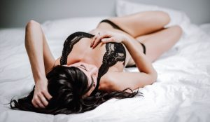 Woman laying in bed with black lingerie, Kitsap WA Boudoir Photography