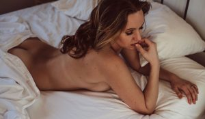 Woman laying in bed with a sheet draped over her, Kitsap WA Boudoir Photography
